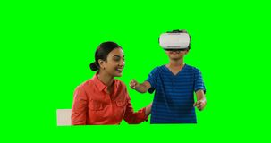 Madre sonriente que ayuda al hijo al usar las auriculares 4k de la realidad virtual almacen de video