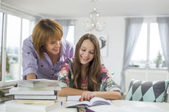 Madre sonriente que ayuda a la hija en hacer la preparación en la tabla Imágenes de archivo libres de regalías