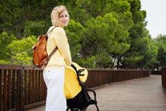 Madre sonriente que da un paseo con recién nacido en carro Fotos de archivo libres de regalías