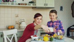 Madre sonriente que hace la foto del selfie así como la hija linda joven que cocina el desayuno en casa en cocina Familia, cocine almacen de video