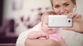 Madre sonriente que hace la foto del selfie con el bebé Mujer con la foto del móvil del niño metrajes