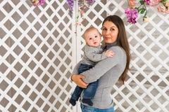 Madre sonriente que juega con el hijo del bebé en casa Fotografía de archivo