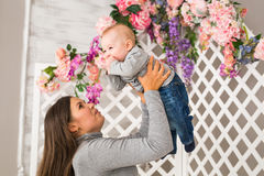 Madre sonriente que juega con el hijo del bebé en casa Imagen de archivo