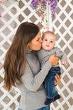 Madre sonriente que juega con el hijo del bebé en casa Fotos de archivo