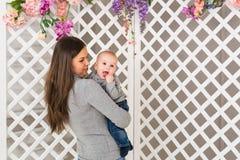 Madre sonriente que juega con el hijo del bebé en casa Imagen de archivo libre de regalías