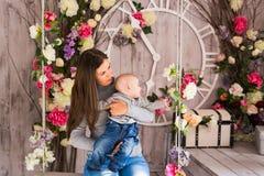 Madre sonriente que juega con el hijo del bebé en casa Imágenes de archivo libres de regalías