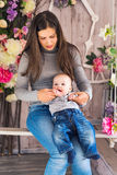 Madre sonriente que juega con el hijo del bebé en casa Foto de archivo