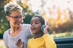Madre sonriente y pequeña hija que se divierten, escuchando la música fotografía de archivo