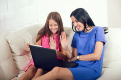 Madre sonriente y su hija que usa un cuaderno Imagen de archivo libre de regalías