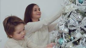 Madre sonriente y su hijo que adornan el árbol de navidad en la sala de estar almacen de video