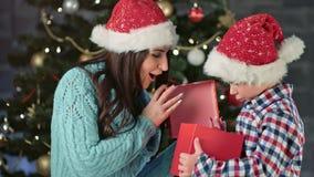 Madre sorridente che dà a bello contenitore di regalo rosso il piccolo Buon Natale stupito sveglio di congratulazione del figlio video d archivio