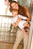 Madre sorridente con il bambino che osserva fuori dall'elevatore Immagine Stock Libera da Diritti