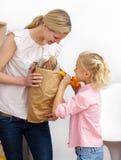 Madre sorridente e la sua bambina che disimballano Immagine Stock