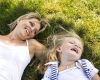 Madre sorridente e piccola figlia sulla natura. Gente felice all'aperto Immagini Stock