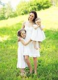 Madre sorridente felice che abbraccia due bambini di estate soleggiata Fotografia Stock Libera da Diritti
