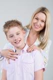 Madre sorridente felice che abbraccia giovane figlio fotografia stock