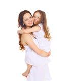 Madre sorridente felice che abbraccia la figlia del piccolo bambino su bianco fotografia stock libera da diritti