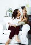 Madre sorridente felice con il piccolo interno sveglio della figlia a casa, fotografia stock