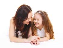 Madre sorridente felice con la figlia del piccolo bambino su bianco Immagini Stock