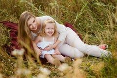 Madre sorridente felice con la figlia sulla natura, famiglia felice Fotografie Stock Libere da Diritti