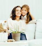 Madre sorridente felice con la piccola figlia sveglia a casa interna, famiglia reale moderna di sembrare casuale, la gente di sti Immagine Stock