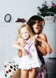 Madre sorridente felice con la piccola figlia sveglia a casa interna, famiglia reale moderna di sembrare casuale, la gente di sti Fotografia Stock Libera da Diritti