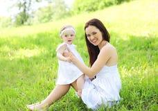 Madre sorridente felice e fare da baby-sitter sull'erba Fotografie Stock Libere da Diritti