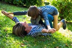 Madre spensierata che gioca con suo figlio adolescente in natura fotografie stock