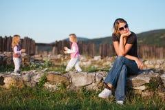 Madre stanca che si siede sulle rocce che hanno resto dallo sforzo quotidiano della famiglia fotografia stock