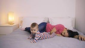 Madre stanca che si trova sul letto che esamina il suo bambino stock footage