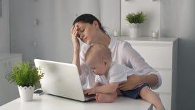 Madre stanca con il bambino che lavora al computer portatile stock footage