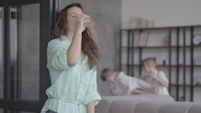 Madre stanca del ritratto giovane che prova a calmarsi che sta vicino alla parete con bicchiere d'acqua mentre i suoi figli teena archivi video