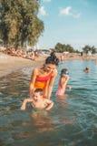 Madre, su hijo e hija jugando y divirtiéndose en el agua imagenes de archivo