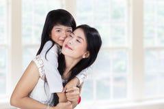 Madre sveglia di abbraccio della ragazza nella casa Fotografia Stock Libera da Diritti