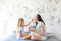 Madre sveglia e figlia sorridenti che applicano la crema di fronte fotografie stock