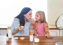Madre sveglia e figlia sorridenti che applicano la crema di fronte fotografia stock libera da diritti