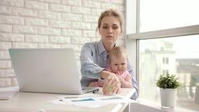 Madre trabajadora con el bebé en la tabla Mamá de funcionamiento con el niño hermoso en las manos almacen de video