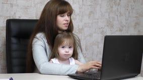 Madre trabajadora con su pequeña hija en la tabla Mujer ocupada que trabaja en el ordenador portátil con el bebé en las manos Mam almacen de video