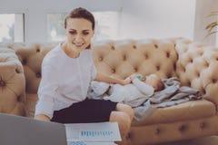 Madre trabajadora joven en el permiso por maternidad que pone su dormir del pequeño niño imagenes de archivo