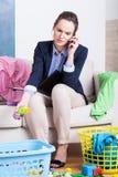 Madre trabajadora joven que habla en el teléfono Imagen de archivo libre de regalías