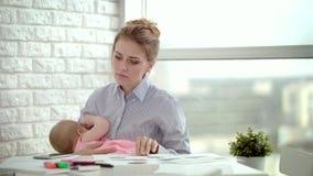 Madre trabajadora que celebra al bebé durmiente en las manos Mamá cansada que trabaja con los documentos metrajes