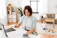 Madre trabajadora que cuenta en la calculadora y el bebé imagen de archivo libre de regalías