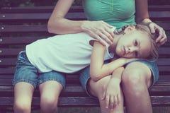 Madre triste e hija que se sientan en banco en el parque fotos de archivo