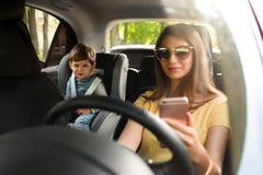 Madre usando el teléfono mientras que conduce el coche con su hijo en asiento trasero fotografía de archivo libre de regalías