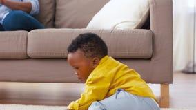 Madre usando la PC de la tableta y beb? que juega bloques del juguete metrajes