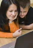 Madre y adolescente con la computadora portátil Fotografía de archivo
