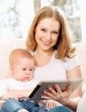Madre y bebé con el ordenador de la tableta en el sofá en casa Foto de archivo libre de regalías