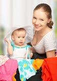 Madre y bebé con la maleta y la ropa listas para el traveli Foto de archivo libre de regalías