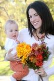 Madre y bebé con las flores - tema de la caída Imágenes de archivo libres de regalías