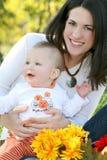 Madre y bebé con las flores - tema de la caída Imagen de archivo